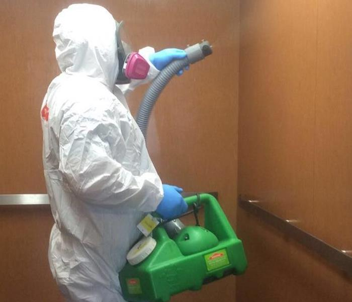 A person in full PPE fogging the inside of an elevator
