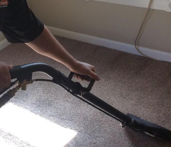 Person using wand to clean carpet