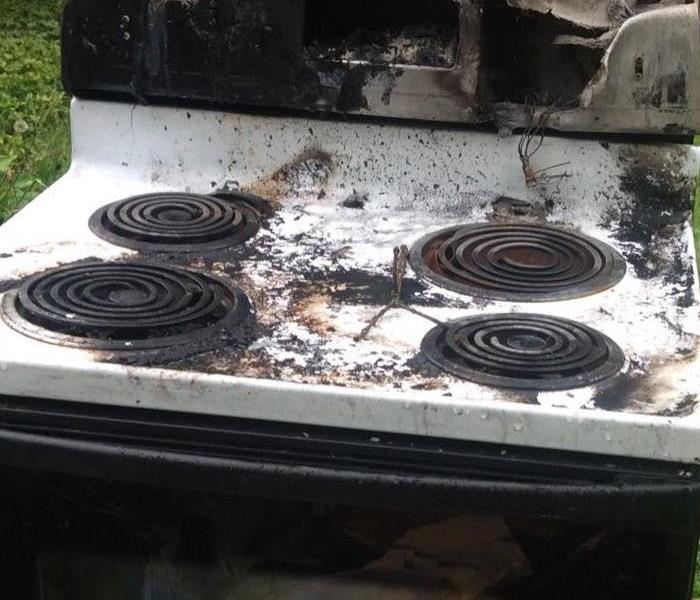 Burned white stove with melted top and charred areas around electric burners