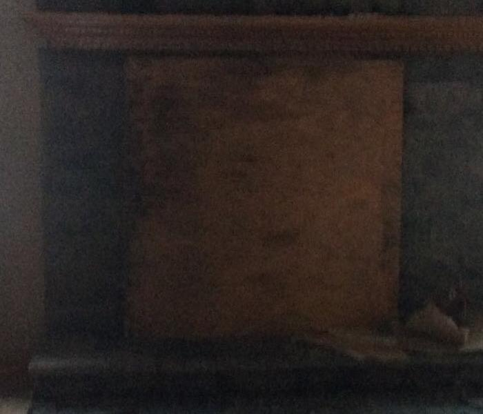 A burned fireplace with a board over the opening with soot and burned floor and other materials around it