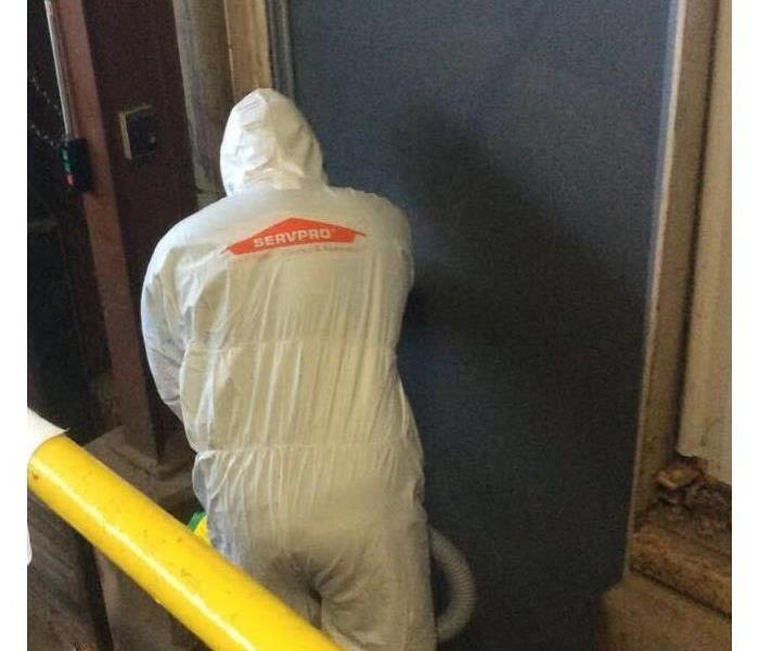 SERVPRO technician fogging door of a facility in full PPE