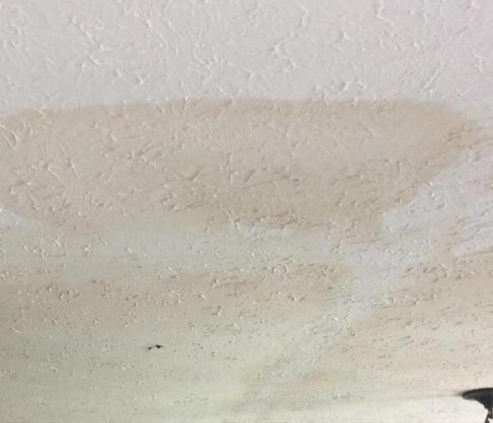 A ceiling with many water marks all over it